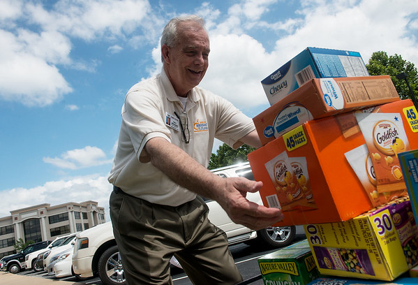 Globe/Roger Nomer<br /> Dale Peterson, Joplin Bright Futures interim director, loads food donations from Arvest Bank on Tuesday.