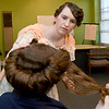 Emily Ellis wraps older sister Kay Ellis' hair around a hairform in a style used to support the Merry Widow Hat, a large hat popular around 1909.<br /> Globe | Laurie Sisk