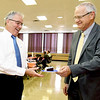 Retiring R-VIII Interim Suerintendent Norm Ridder hands a slice of cake to fellow retiree, R-VIII Chief Financial Officer Paul Barr during a retirement reception for the two school officials on Tuesday at the Memorial Education Center. Ridder came out of retirement to lead the district during their search for a permanent superintendent. Barr worked for the district for 23 years. <br /> Globe | Laurie Sisk