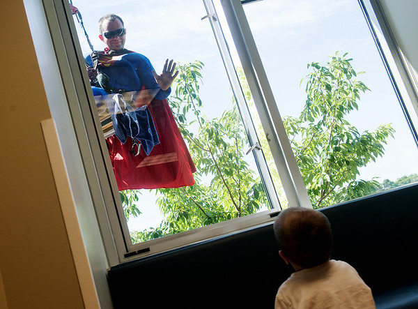 Globe/Roger Nomer<br /> Joe Callaway, with Clearview Window Cleaners, waves to Jaxxson Marcum, 2, while cleaning windows at Freeman Hospital West on Monday morning. Window cleaners dressed up as Superman and other superheroes to entertain patients.