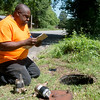 Globe/Roger Nomer<br /> Carze Brown, assitant director of public works in Carterville, replaces a water meter on Friday.