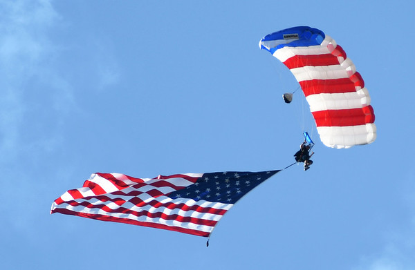 Accompanied by the National Anthem, parachutist Steve Stewart, of Skydive Airtight in Skiatook, Ok., kicks off the Celebrate Neosho Air Show on Saturday at Neosho's Hugh Robinson Airport. The day-long event featured carnival rides, vendors, helicopter rides, tandem sky diving and more. The excitement was capped off by a large airshow and fireworks display. As many as 5,000 spectators were expected to attend the fourth annual event.<br /> Globe | Laurie Sisk