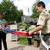 From the left: Boy Scout Troop 103 scouts Michael Bowman, 15, and Riley Bowers, 14 begin to fold a flag into triangles as they demonstrate the proper protocol for folding an American flag on Tuesday afternoon at Spiva Park.<br /> Globe | Laurie Sisk