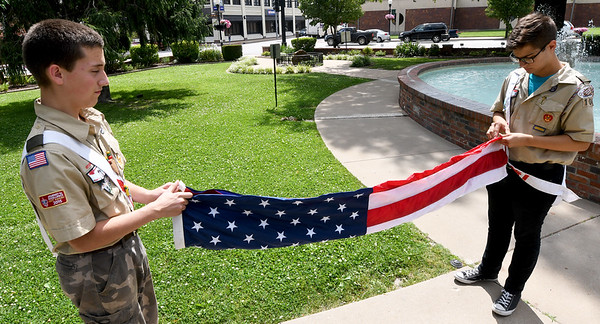 From the left: Boy Scout Troop 103 scouts Riley Bowers, 14 and Michael Bowman, 15, demonstrate the proper protocol for folding an American flag on Tuesday afternoon at Spiva Park.<br /> Globe | Laurie Sisk