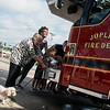 Globe/Roger Nomer<br /> Milly Boen and her dog Spunky help Joplin Councilmember Melodee Colbert-Kean and other Joplin officials and residents push in the new fire truck on Monday at the Main Street fire station.