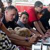 Globe/Roger Nomer<br /> Chuckie Jennings, center, helps push in the new fire truck on Monday at the Main Street station.