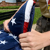 Boy Scout Riley Bowers, 14, of Troop 103 folds a flag into triangles as they demonstrate the proper protocol for folding an American flag on Tuesday afternoon at Spiva Park.<br /> Globe | Laurie Sisk
