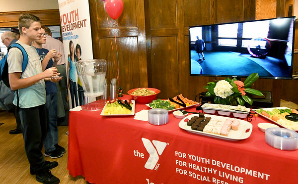 From the left: Twin 13-year-old brothers Brendon and Brenton Mynatt check out a video of the Downtown YMCA on Wednesday afternoon at a reception ahead of the closing of the location.<br /> Globe | Laurie Sisk