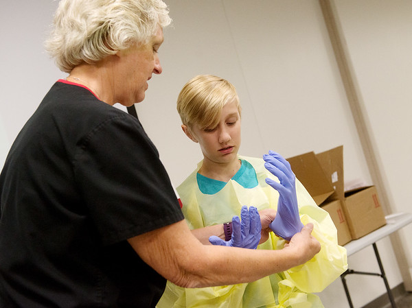 Globe/Roger Nomer<br /> Donna Stokes, an infection preventionist with Mercy Hospital Joplin, helps Dylan Oakes, 12, Joplin, with his gloves and gown before a dissection project on Thursday at Mercy. The dissection was part of Mercy's summer MASH Camp 2017, presented by the Southwest Missouri Area Health Education Center.