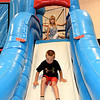 Zach Pennington enjoys a slide down an inflatable castle as Phoebe Estes, 6, waits her turn during summer school on Friday at Wildwood School. The play day is one of many perks of attending summer school in the district. <br /> Globe | Laurie Sisk