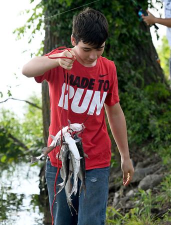 !4-year-old Daniel Moore holds his stringer of catfish during Kid's Fishing Day on Saturday at Kellogg Lake in Carthage. The event featured information booths, activities, food and fishing - all free of charge to guests.<br /> Globe | Laurie Sisk