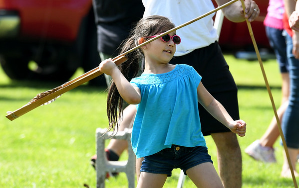 Six-year-old Sofia Velazco uses an atlatl, to launch a large spear used for hunting at a booth sponsored by the Missouri Department of Conservation during Kid's Fishing Day on Saturday at Kellogg Lake in Carthage. The event featured information booths, activities, food and fishing - all free of charge to guests.<br /> Globe | Laurie Sisk