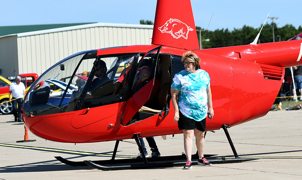 Sheila Drake, of Joplin, exits a helicopter after her first-ever ride on Saturday during the Celebrate Neosho Air Show at Neosho's Hugh Robinson Airport. The day-long event featured carnival rides, vendors, helicopter rides, tandem sky diving and more. The excitement was capped off by a large airshow and fireworks display. As many as 5,000 spectators were expected to attend the fourth annual event.<br /> Globe | Laurie Sisk