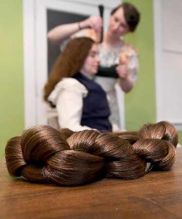 Younger sister Emily Ellis uses a hairform to style Kay Ellis' hair in a style used to support the Merry Widow Hat, a large hat popular around 1909.<br /> Globe | Laurie Sisk