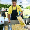 Howard Burnison, of King's Kettle Corn, scoops fresh bags of popcorn for guests at Nan's Band-Aid on Saturday at Schifferdecker Park. Proceeds of the event will go to help the 40 employees who lost their jobs after a fire at the Joplin Workshops laundry. The event was named after the late Nancy Clarkson, longtime employee at the workshop.<br /> Globe | Laurie Sisk