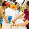 Sarah Serio helps Rachel Severin, 8, with a comic book holder during Thursday's Superhero Adventures Camp at Spiva Center for the Arts.<br /> Globe | Roger Nomer