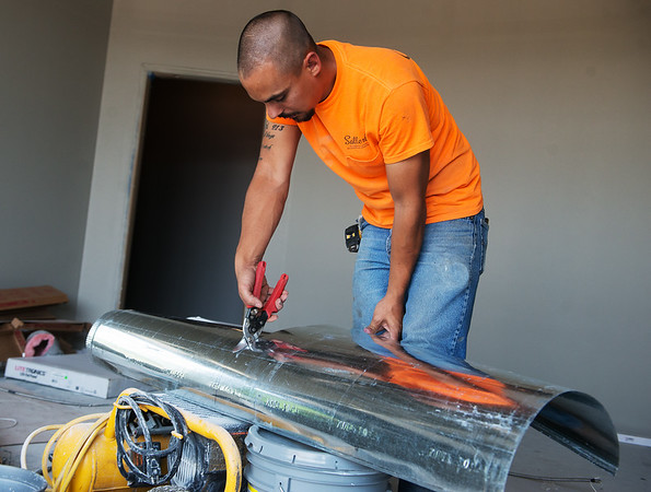 Zack Kutz, a sheet metal installer with Satterlee, works at the new Joplin VA outpatient clinic on Monday.<br /> Globe | Roger Nomer