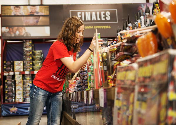 Sarah Russel, 16, Carl Junction, stocks fireworks at the Carl Junction FFA store on North Main in Joplin on Monday.<br /> Globe | Roger Nomer