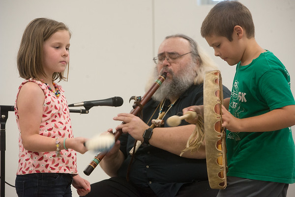 Claire Gould, 7, and Charlie White, 8, accompany flutist Mark Barger on Tuesday at the Joplin Public Library.<br /> Globe | Roger Nomer