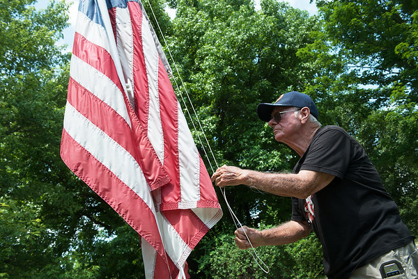 Charles Surgi demonstrates one of his flagpoles at his home in Joplin on Wednesday.<br /> Globe | Roger Nomer