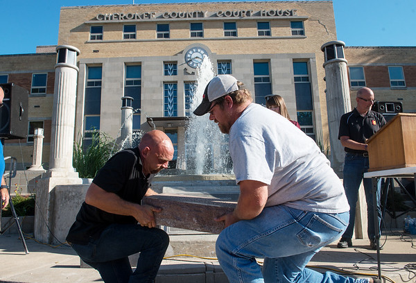 Alan Garmany, left, and Justin Rogers, both with the City of Columbus, lift the headstone for the 1968 time capsule at the Cherokee County Courthouse on Saturday.<br /> Globe | Roger Nomer