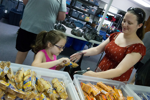 Robin Gilmore, 5, and her mother Kacey put together a snack pack at Carthage Bright Futures on Tuesday morning. The snack packs are taken home by students identified as food insecure over the weekend during summer school. Volunteers can help assemble the snack packs the next two Tuesdays.<br /> Globe | Roger Nomer