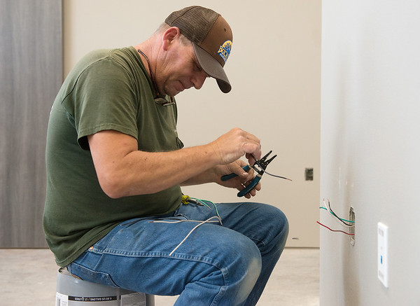 Mike Tuckett, a journeyman electrician with Layne Electric, works at the new Joplin VA outpatient clinic on Monday.<br /> Globe | Roger Nomer