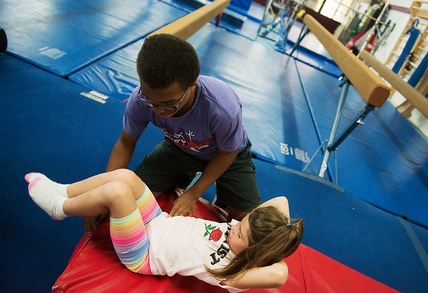 Dominic Dumas, 14, helps Sierra Duncan, 6, with her tumbling technique during the Back Handspring Camp at The Flip Shop on Monday morning.<br /> Globe   Roger Nomer