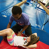 Dominic Dumas, 14, helps Sierra Duncan, 6, with her tumbling technique during the Back Handspring Camp at The Flip Shop on Monday morning.<br /> Globe | Roger Nomer