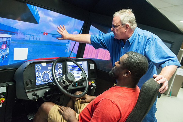 Marco Johnson, a Crowder student from Lakeland, Fla., works with Darrin Pfeifly, director of Crowder Transport Training, on a driving simulator on Thursday at Crowder.<br /> Globe   Roger Nomer