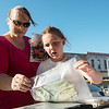 Tina England, Columbus, and her niece Emily Burton, 6, look over items left in the 1968 time capsule in Columbus on Saturday.<br /> Globe | Roger Nomer