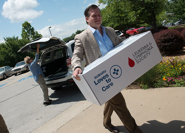 Georgia Turner, encore specialist at Frank Fletcher Subaru, and Brent Lobanoff, executive vice president and partner at Frank Fletcher Subaru, deliver blankets, craft kits and messages of hope to the Freeman Cornell-Beshore Cancer Institute on Wednesday. <br /> Globe | Roger Nomer