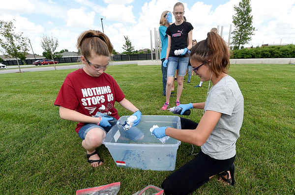 Twelve -year-old El Allender, left and Rayann Meredith, 12, right, squirt dye on shirts as Acadia Badgly, 13, looks on during the Joplin Public Library's annual Tie Dye Fest on Tuesday afternoon on the library lawn. The event was part of the teen department's programs at the library.<br /> Globe   Laurie SIsk