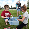Twelve -year-old El Allender, left and Rayann Meredith, 12, right, squirt dye on shirts as Acadia Badgly, 13, looks on during the Joplin Public Library's annual Tie Dye Fest on Tuesday afternoon on the library lawn. The event was part of the teen department's programs at the library.<br /> Globe | Laurie SIsk
