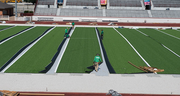 Workers with Astroturf install new turf at Junge Stadium on Monday as they prepare the playing surface for fall football.<br /> Globe | Roger Nomer