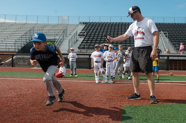 Outlaws player Parker Dunn times Kale Metcalf as he runs the bases during Wednesday's youth camp at Joe Becker Stadium.<br /> Globe   Roger Nomer