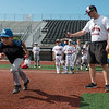 Outlaws player Parker Dunn times Kale Metcalf as he runs the bases during Wednesday's youth camp at Joe Becker Stadium.<br /> Globe | Roger Nomer
