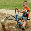 Four-year-old Beau Haslip uses the toy backhoe at Parr Hill Park on Saturday. The park also features a spray park, dog park and outdoor gym equipment.<br /> Globe | Laurie SIsk