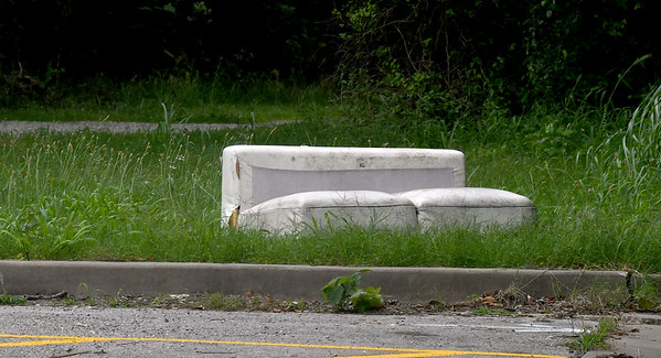A discarded sofa sits near the trail head of the Frisco-Greenway trail on Saturday.<br /> Globe | Laurie Sisk