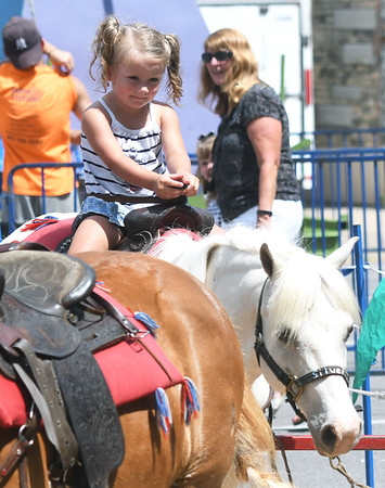 Two-year-old Raelynn Garren, of Goodman, enjoys a pony ride during Celebrate Neosho on Saturday on the Neosho Square. The event kicks off a host of Fourth of July events in the Four State area.<br /> Globe | Laurie Sisk