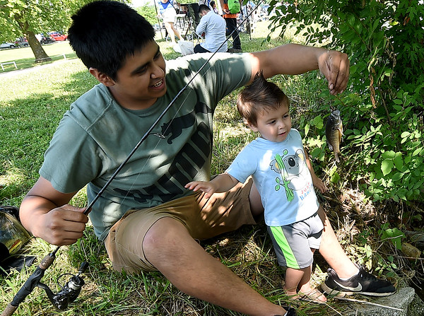 Two-year-old Billy Artega reacts to his first solo catch - a tiny sunfish- as his father, Louis Artega prpeares to take it off the line during the annual Kids Fishing Day on Saturday at Carthage's Kellogg Lake. The annual event featured free fishing, educational booths, free lunch and more.<br /> Globe | Laurie Sisk
