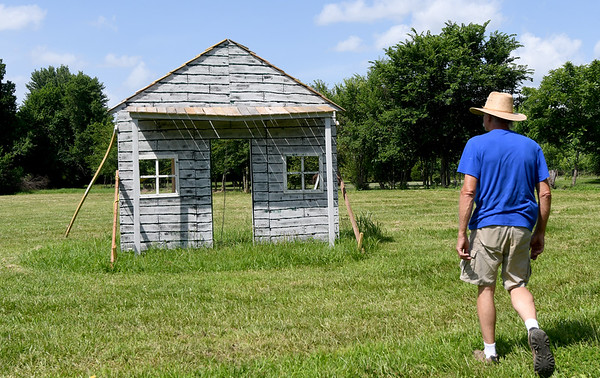 Steve Maddox walks near a mock up of what the Rader house probably looked like during the Civil War. The house is located at the Sherwwod-Rader Farm near Carl Junction.<br /> Globe   Laurie SIsk