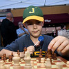 Eight-year-old Caleb Davenport ponders his next move on the chess board at the Titanic Museum booth at Third Thursday last Thursday in downtown Joplin.<br /> Globe | Laurie Sisk