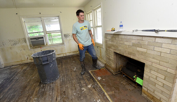 Zachary Moore, of Moore Construction, works to try and rehabiliate a previously flooded home  on the 1100 block of Central Ave. in Miami on Wednesday.<br /> Globe | Laurie SIsk
