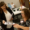 Shannon Creighton, attorney and partner with Gilmore & Bell, distributes information to Stacy Daniels, mayor of Miller, during Thursday's Missouri Department of Natural Resources financing workshop at the Route 66 Event Center in Webb City.<br /> Globe | Roger Nomer
