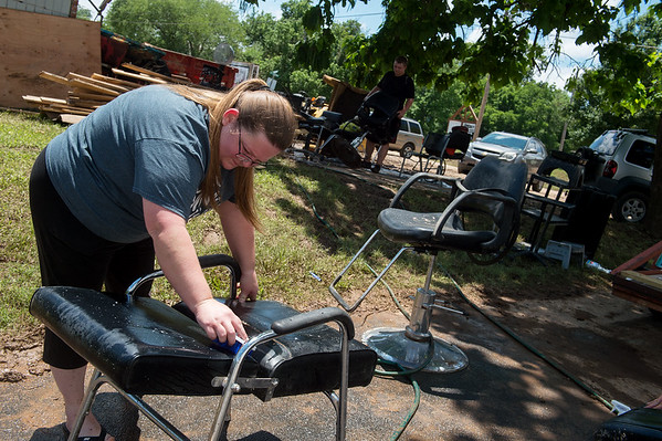 Amber Brooks cleans mud off of a chair at Southern Roots salon on Tuesday in Anderson.<br /> Globe | Roger Nomer