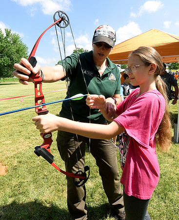 Ten-year-old Zxander Canady, of Carthage, tries her hand at archery with the assistance of Missouri Department of Conservation volunteer Regina Chavis during the annual Kids Fishing Day on Saturday at Carthage's Kellogg Lake. The annual event featured free fishing, educational booths, free lunch and more.<br /> Globe | Laurie Sisk