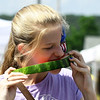 Adison McReynolds, 12, of Neosho, enjoys a cold slice of watermelon during Celebrate Neosho on Saturday on the Neosho Square. The event kicks off a host of Fourth of July events in the Four State area.<br /> Globe | Laurie Sisk
