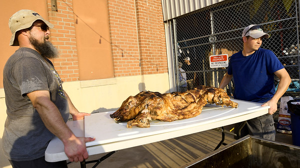 From the left: Marty Yates, of The Bearded Baker and Shane Ferguson, of Blackcat Barnyards, carry a large cutting board with an 80-lb. roasted pig to be carved and served to patrons during the Empire Market's Summer Solstice Night Market on Friday night at the market. About 1,350 people attended the event, which featured a variety of vendors, cash bar, music and more.<br /> Globe | Laurie Sisk