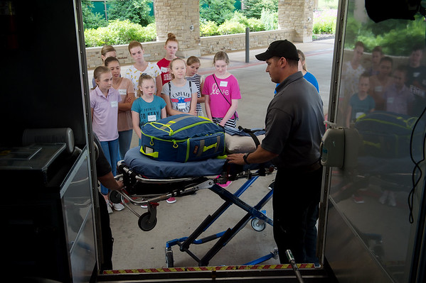 Jesse Merritt, paramedic with Mercy Hospital, gives a tour of an ambulance during Monday's MASH Camp at Mercy Hospital.<br /> Globe | Roger Nomer